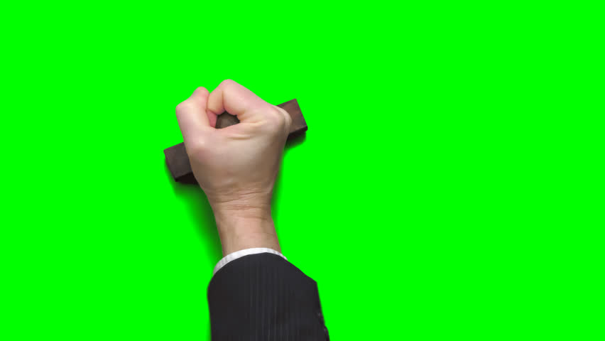 Businessman's hand stamping blank messages with a rubber stamp onto a chroma key green background. Alpha channel included for easy background replacement.