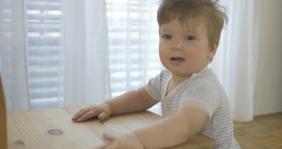 Handheld shot of an adorable baby doing baby stuff at home.    Shutterstock HD Video #22724494