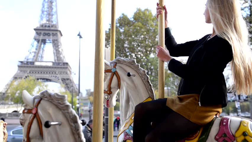 Young blonde woman portrait smiling and having fun on carousel in front of the Eiffel Tower in Paris, France. | Shutterstock HD Video #22734835