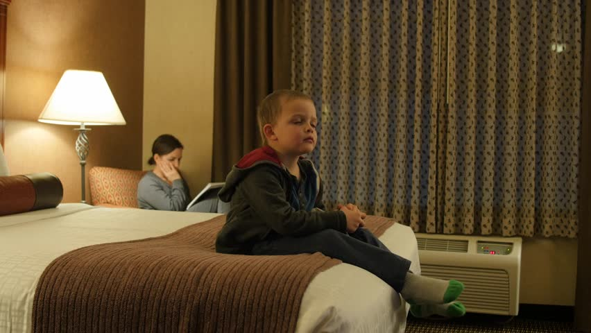 Adorable little boys watching the Television in their hotel room at night with their family #22935787