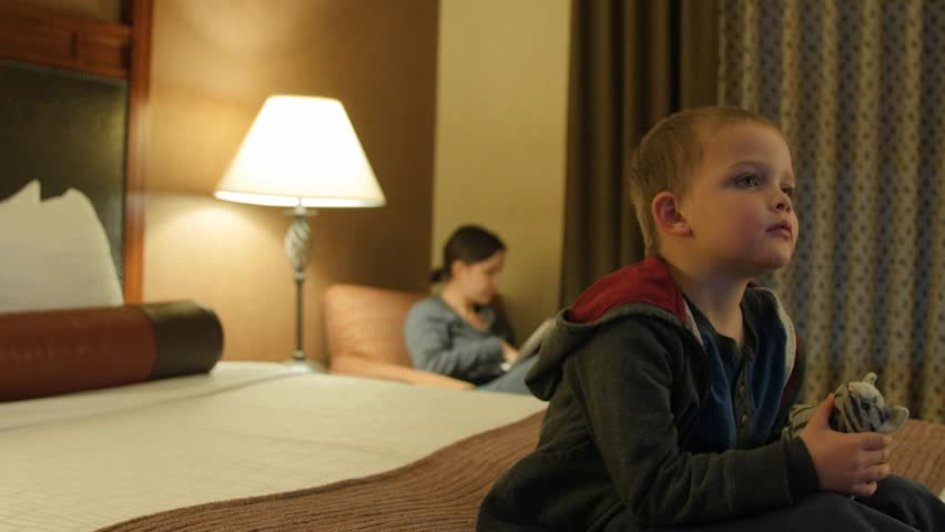 Adorable little boys watching the Television in their hotel room at night with their family #22935796