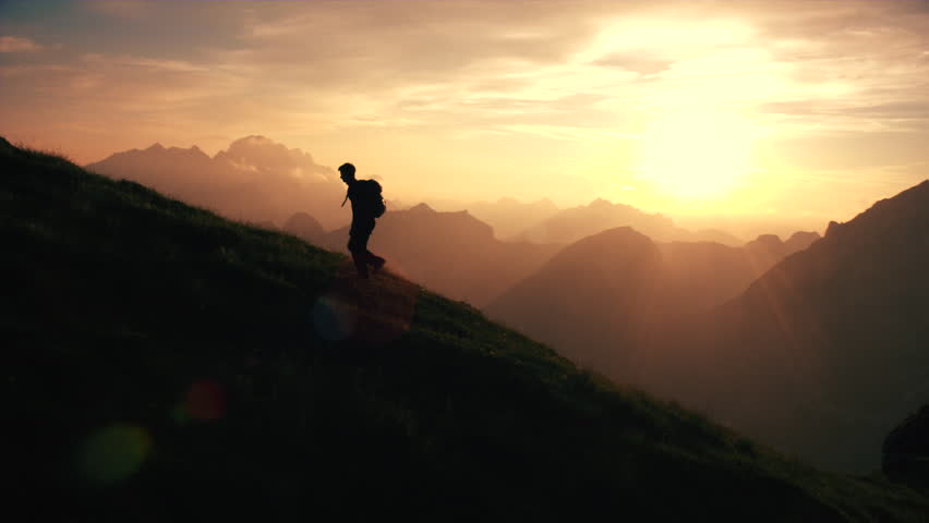 Aerial, edited - Epic shot of a man hiking on the edge of the mountain as a silhouette in beautiful sunset | Shutterstock HD Video #22952905