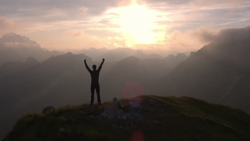 Aerial - Flyover silhouette of a man standing on top of the mountain. Man raising arms victoriously after climbing the mountain | Shutterstock HD Video #22960843