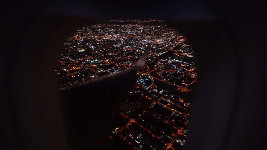 Aerial view from airplane window over Los Angeles City Lights on approach to landing at airport | Shutterstock HD Video #23069356