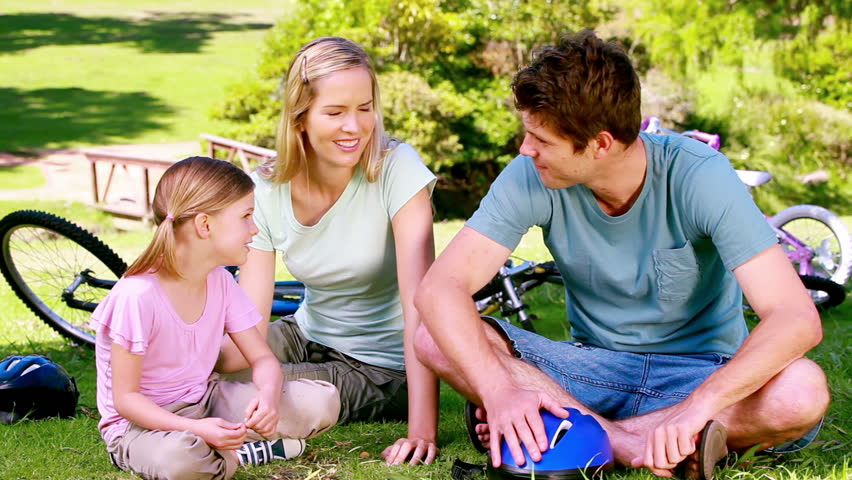 Girl with her parents with bikes sitting in a park - HD stock footage clip