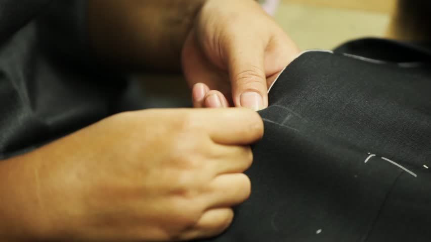 Sewing a button onto a bespoke tailored suit | Shutterstock HD Video #23112259