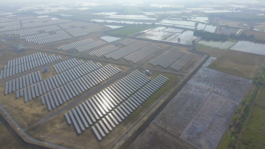 Aerial View of Solar Panels in Solar Power Station with Sunlight. Orbit shot with Drone.   Shutterstock HD Video #23113321