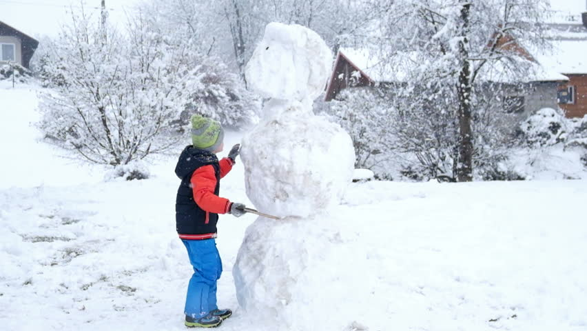 Little boy playing with snow ball of snowman in winter  | Shutterstock HD Video #23135479