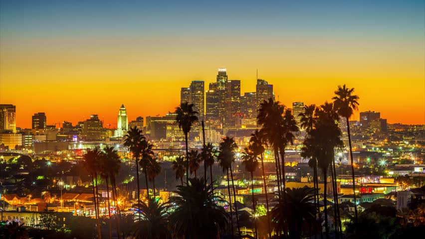 Dusk to night transition, zoom in on city of Los Angeles downtown skyline with palm trees silhouettes in foreground. 4K UHD timelapse. | Shutterstock HD Video #23151454