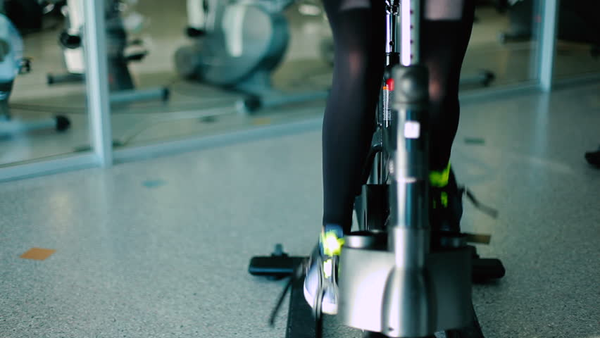 Slim sports legs pedaling on the exercise bike in the gym | Shutterstock HD Video #23163361