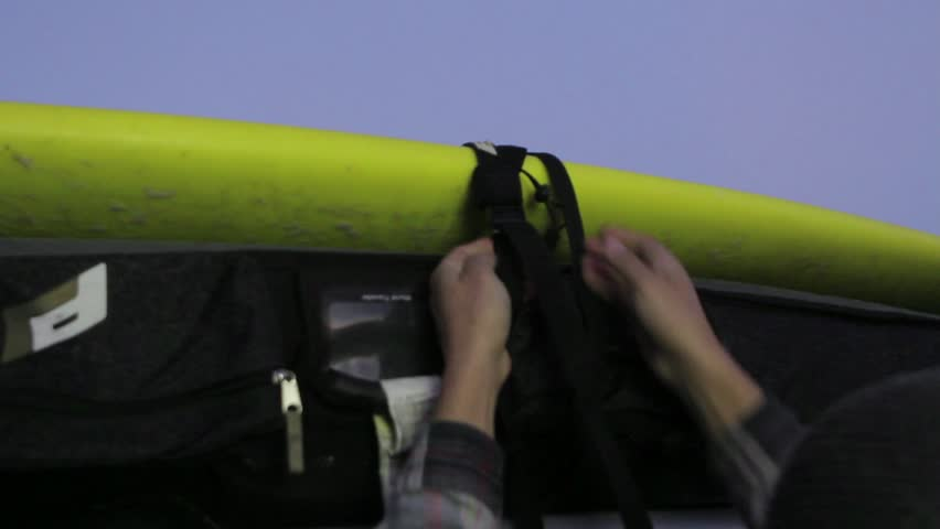 A close up shot of a man's hands as he secures a surf board to the roof of his car. (Santiago, Chile - Feb 2016) | Shutterstock HD Video #23171686