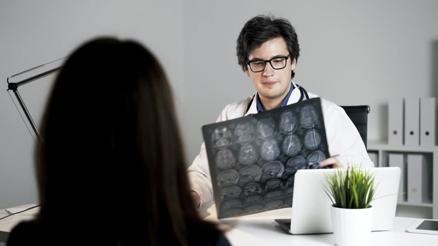 A doctor is discussing the diagnosis with the patient, neurologist is holding a brain x-ray. A concept of successful medical practice. Locked down real time medium shot.  | Shutterstock HD Video #23211997