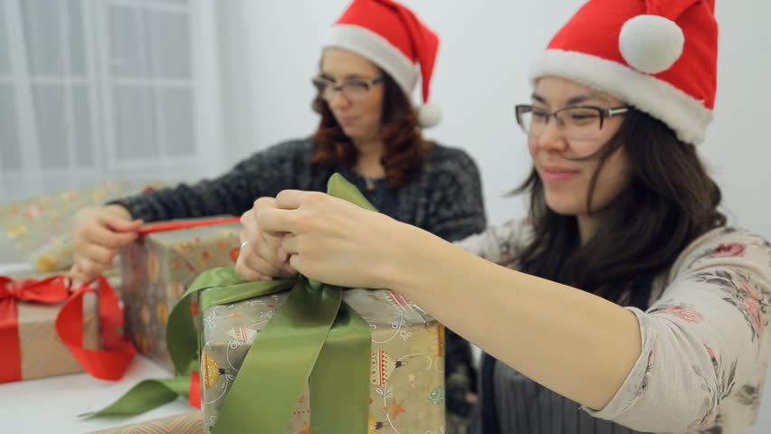 Two women decorate gifts with bows for Christmas, New Year. In front of us Asian with black flowing hair, in sweater with flower pattern, gray apron, with silver ring on right hand tries to tie bow of | Shutterstock HD Video #23213167