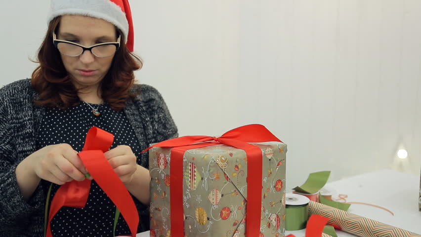 Woman makes bow gifts for Christmas, New Year. Female with red curly flowing hair in gules hat white fur around face and small ball at top, glasses in dark frame, in black sweater, with pendant with | Shutterstock HD Video #23213185