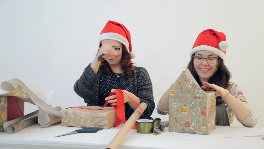 Two charming women pack Christmas gifts. Cute brunette in red New Year cap trimmed with white fur and black square glasses works intently to create festive atmosphere and good mood. Elf of Santa Claus | Shutterstock HD Video #23213194
