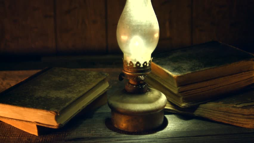 Old oil lamp and old books in darkness. Vintage kerosene lantern and old book on wooden table. 4K UHD video footage, dolly shot. Ultra high definition 3840X2160 | Shutterstock HD Video #23267788
