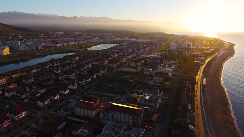 Aerial View. Flying over the city buildings houses sea near the beach on a sunny day. Sochi Adler olympiad. Aerial drone shot. 4K 30fps ProRes (HQ) | Shutterstock HD Video #23311069