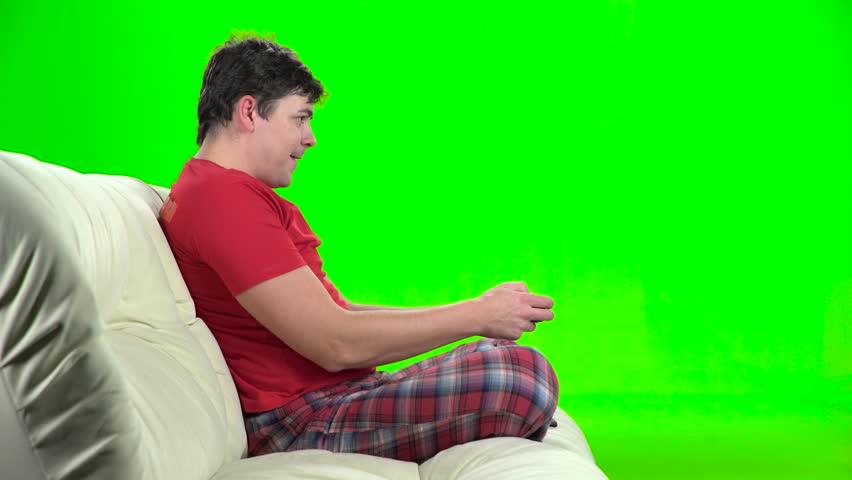 Man playing videogames with gamepad sitting on couch. Green screen | Shutterstock HD Video #23323372
