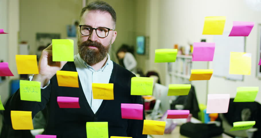 Portrait of a smiling man in a thoughtful and creative agency with colorful notes and planning hanging behind the glass and the working people. Concept: team work, agency, creative, business | Shutterstock HD Video #23374438
