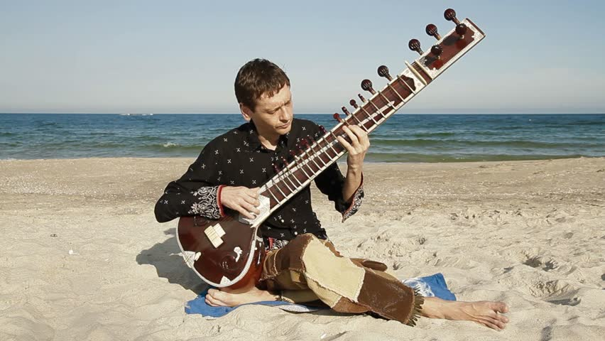Man plays the sitar on the beach - HD stock footage clip