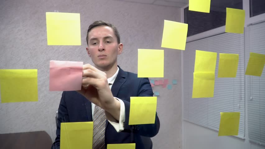 Businessman writing on sticky notes in office | Shutterstock HD Video #23498188