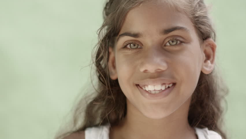 Portrait of latina woman, young girl with green eyes smiling and looking at camera