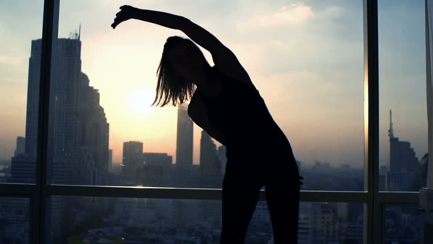 Silhouette of woman exercising bend by window during sunset at home  | Shutterstock HD Video #23524522