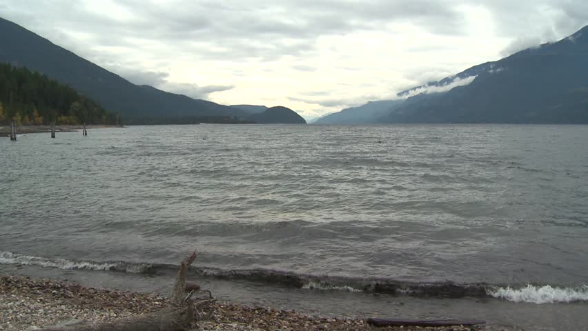 BRITISH COLUMBIA ca.2015, Kootenay Lake, wide shot establishing. The lake is a long, narrow and deep fjord-like lake located between the Selkirk and Purcell mountain ranges. 104 km (65 mi) long | Shutterstock HD Video #23550010