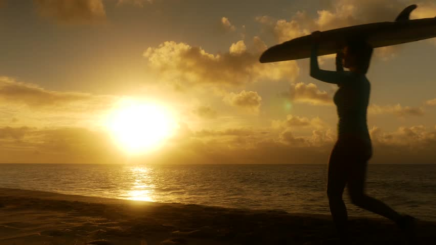 Surfer couple in silhouette walking with long surfboards at sunset on beach | Shutterstock HD Video #23565535