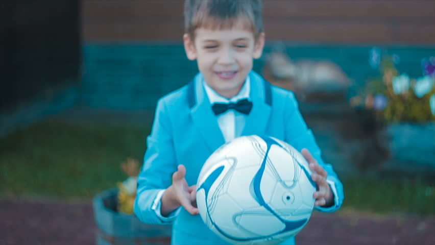 A Smiling Boy, Primary School Age, Playing With a Basketball Trying to Spin it on a Finger, he Fails to do it But Still Enjoys the Game.blue, Green Colors Predominate. Green Grass, Flowerbeds. | Shutterstock HD Video #23598277