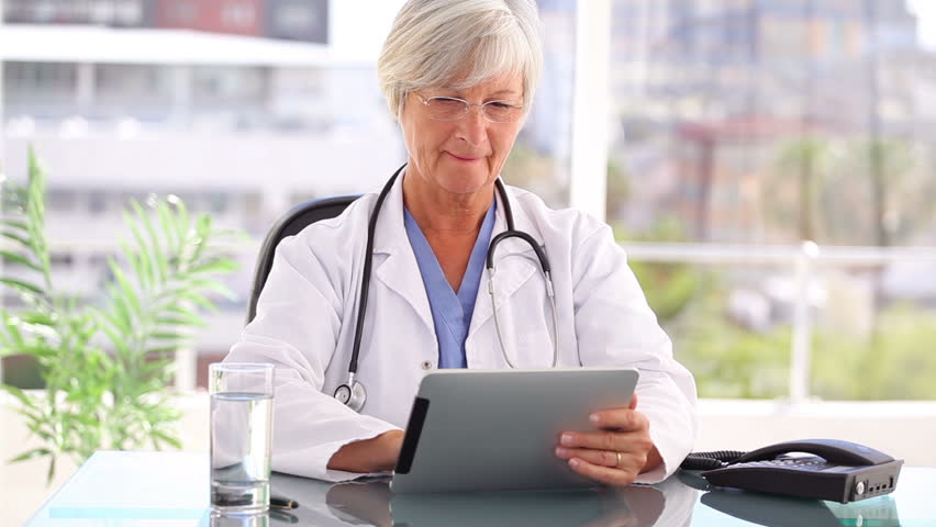 Smiling practitioner holding a tablet computer in a bright office - HD stock footage clip