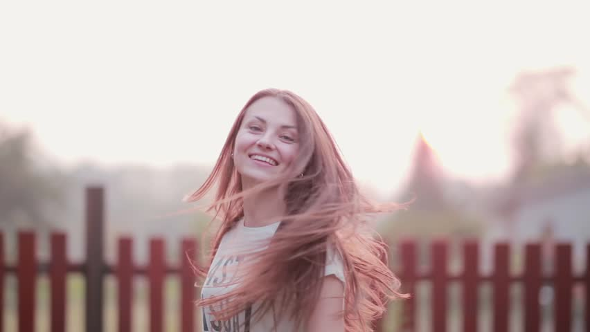 Portrait of beautiful brunette young woman smiling outdoor, turns and looking at camera cheerful on sunset | Shutterstock HD Video #23876458