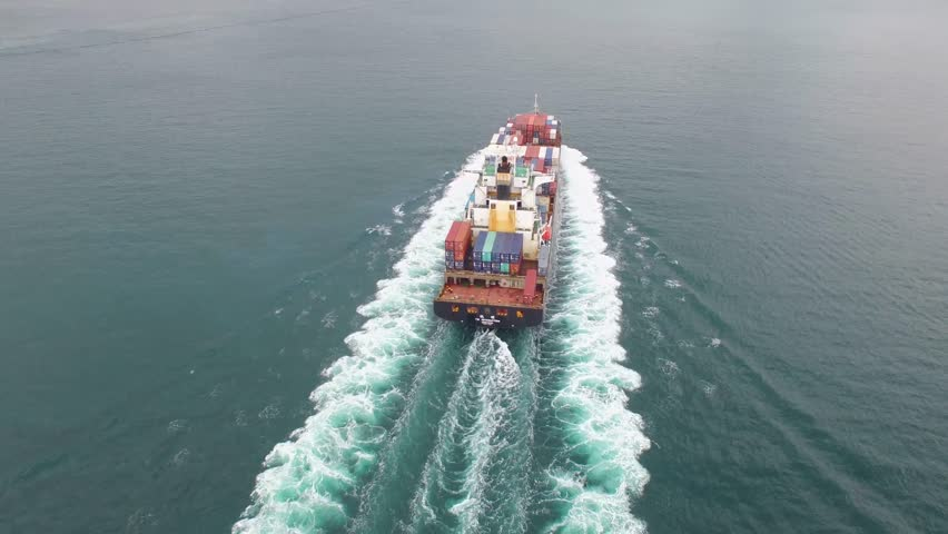 Container freight ship sailing in the calm ocean waves on a cloudy day in 4k aerial shot | Shutterstock HD Video #23936731