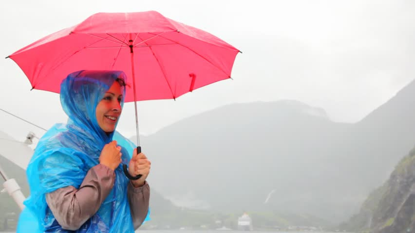woman in blue raincoat and under red umbrella freezes against rocky landscapes - HD stock footage clip