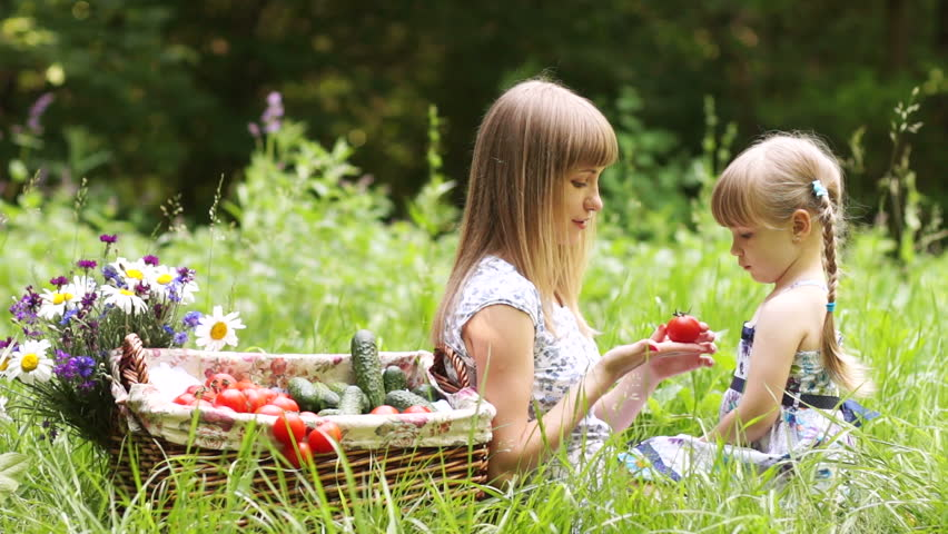 Mother gives baby vegetables. They are outdoors.  - HD stock footage clip