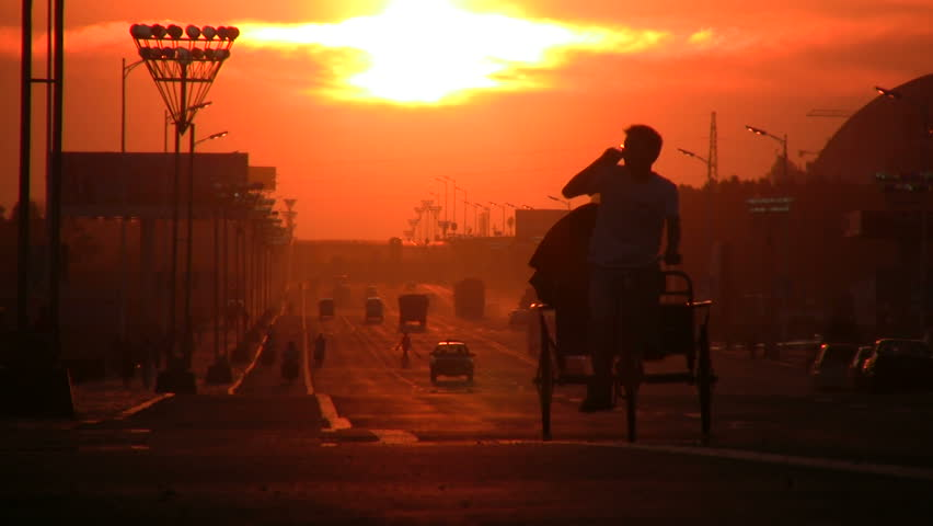 Two people use a tricycle to ride through the streets of Manzhouli at sunset