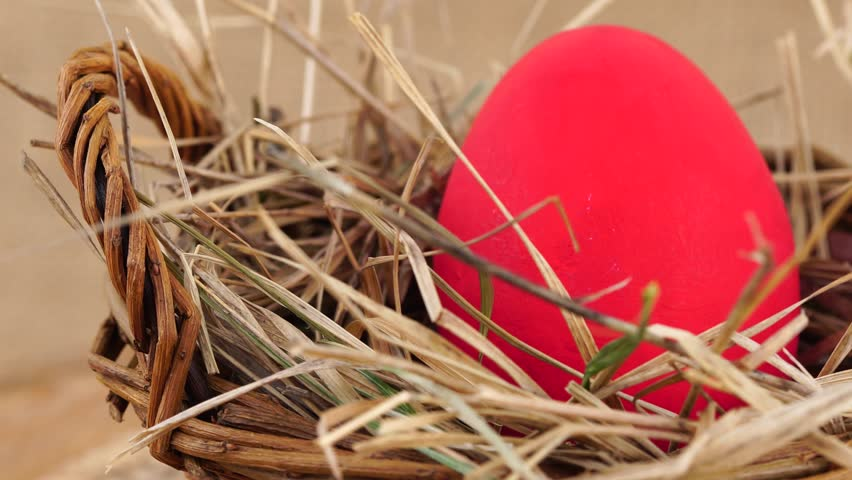 Close up shot of a red Easter egg in woven basket with dry grass rotating against beige background. Egg in a nest concept. | Shutterstock HD Video #24027775