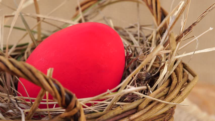 Close up shot of a red Easter egg in woven basket with dry grass rotating against beige background. Egg in a nest concept. | Shutterstock HD Video #24027784