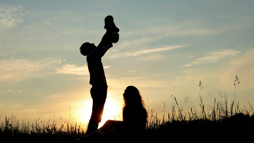 Happy family: father, mother and baby playing at sunset. Silhouettes