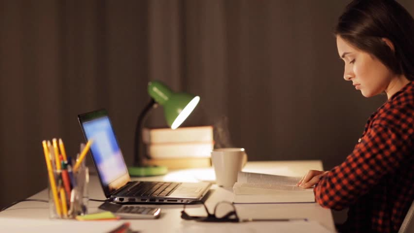 People, education and learning concept - student girl or woman reading book at home at night | Shutterstock HD Video #24056791