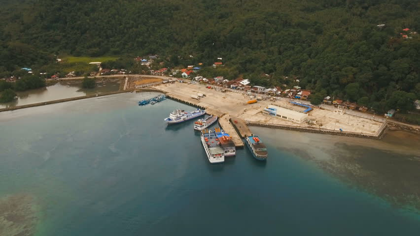Aerial view:passenger ferry terminal with ferry boats.Ferries for transport vehicles and passengers in the port.Sea passenger port on a tropical island.Philippines, Camiguin. 4K video.Travel concept | Shutterstock HD Video #24072595