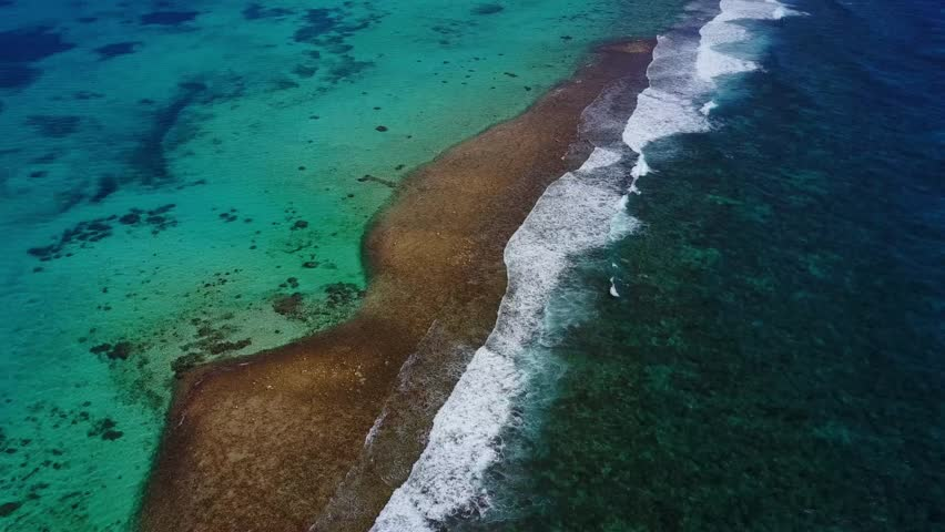 Aerial view high above a barrier reef in the caribbean. waves crashing on the shallow reef and blue green depth changes are striking. East End, Grand Cayman