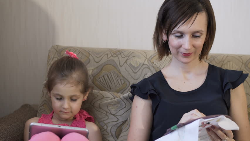 Young caucasian woman embroiders with colored thread sitting on the couch. Next to her little daughter playing with a tablet. | Shutterstock HD Video #24105112