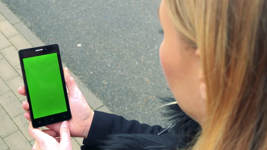 A blonde woman stands on a sidewalk and looks at a smartphone with a green screen | Shutterstock HD Video #24114175