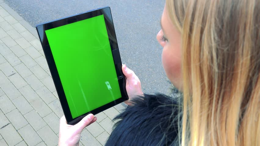 A blonde woman stands on a sidewalk and looks at a tablet with a green screen | Shutterstock HD Video #24114193