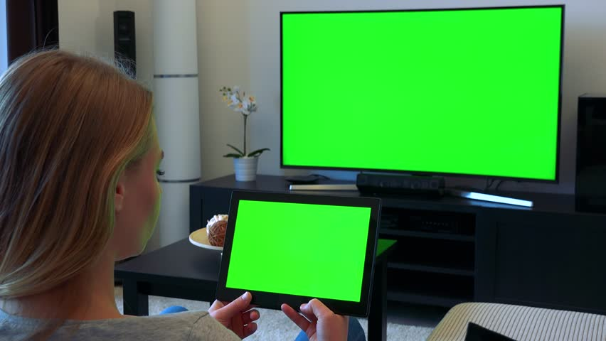 A blonde woman sits on a couch in a living room and looks in turns at a TV and a tablet (both green screen) | Shutterstock HD Video #24114220