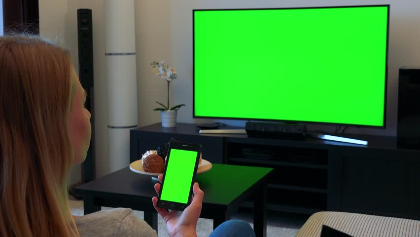 A blonde woman sits on a couch in a living room and looks in turns at a TV and a smartphone (both green screen) | Shutterstock HD Video #24114238