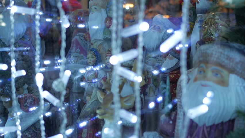 Shop window with figures in traditional russian clothes through bright garland | Shutterstock HD Video #24117415
