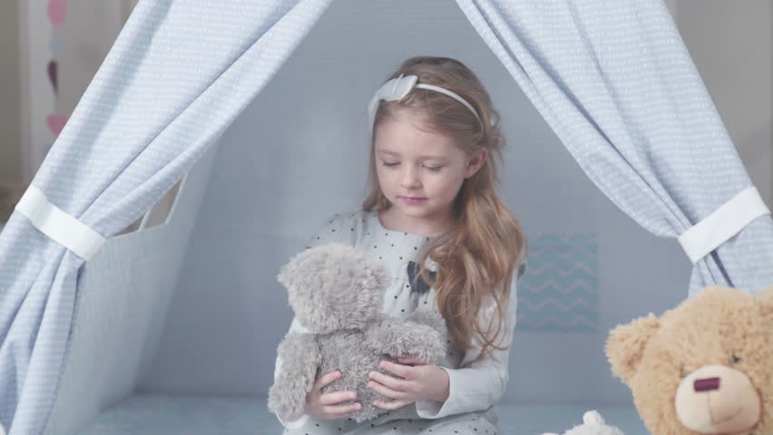 Little cute girl with blond hair sitting in a toy house surrounded by soft toys. Girl playing with a toy hare and a soft teddy bear. Wigwam for children in a room. #24130168