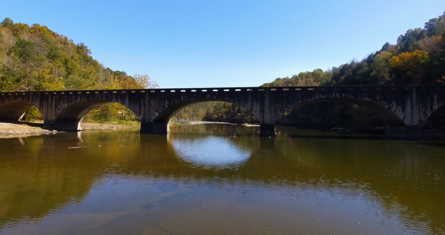 Cinematic shot of an old stone bridge crossing a calm Cumberland River as the camera travels upstream & under the middle arch on a day with a clear blue sky & fall leaves on the trees in mid Autumn.   Shutterstock HD Video #24131725